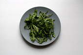 Bundle of arugula salad isolated on gray concrete plate from a high angle view