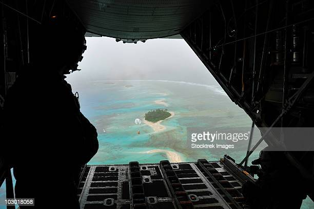 A bundle of donated goods drifts to an island after being dropped out the back of a C-130 Hercules.