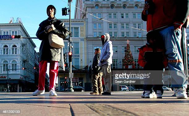 Bundled up in their coats people wait for the Street Car on Canal Street as temperatures in the area plummeted below freezing on January 7 2014 in...
