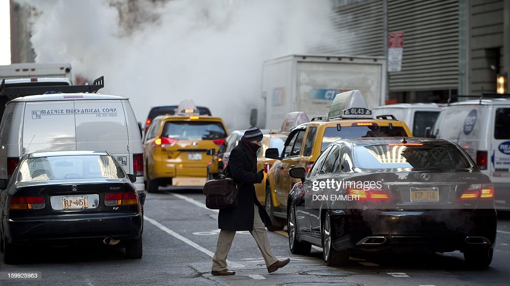 A bundled up man crosses the street through traffic January 23, 2013 in New York. Two-thirds of the US was in the grips of a blast of cold Arctic air Wednesday with temperatures falling to some of the lowest marks in years and wind chills plummeting to dangerously low levels. AFP PHOTO/DON EMMERT