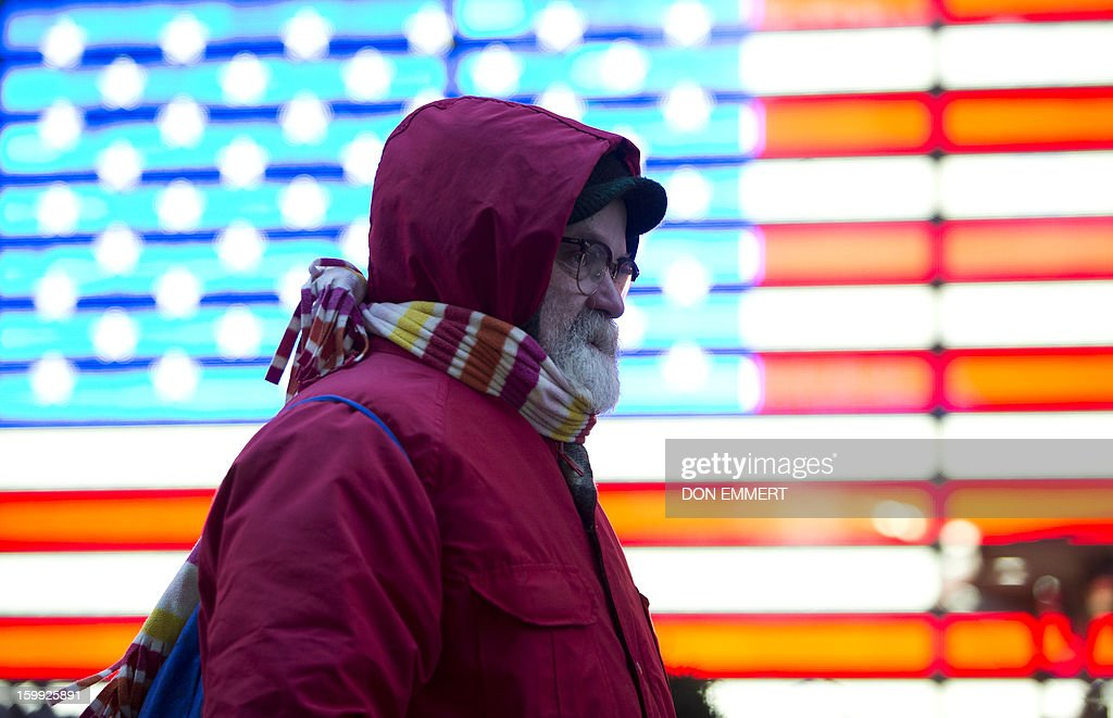 A bundled up man passes an American flag of lights as he walks down the street in Times Square January 23, 2013 in New York. Two-thirds of the US was in the grips of a blast of cold Arctic air Wednesday with temperatures falling to some of the lowest marks in years and wind chills plummeting to dangerously low levels.