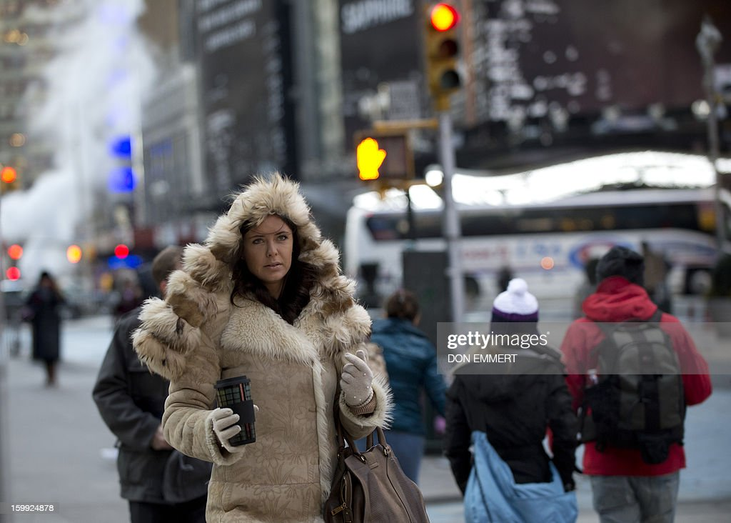 A bundled up woman carries a hot cup while crossing the street in Times Square January 23, 2013 in New York. Two-thirds of the US was in the grips of a blast of cold Arctic air Wednesday with temperatures falling to some of the lowest marks in years and wind chills plummeting to dangerously low levels. AFP PHOTO/DON EMMERT