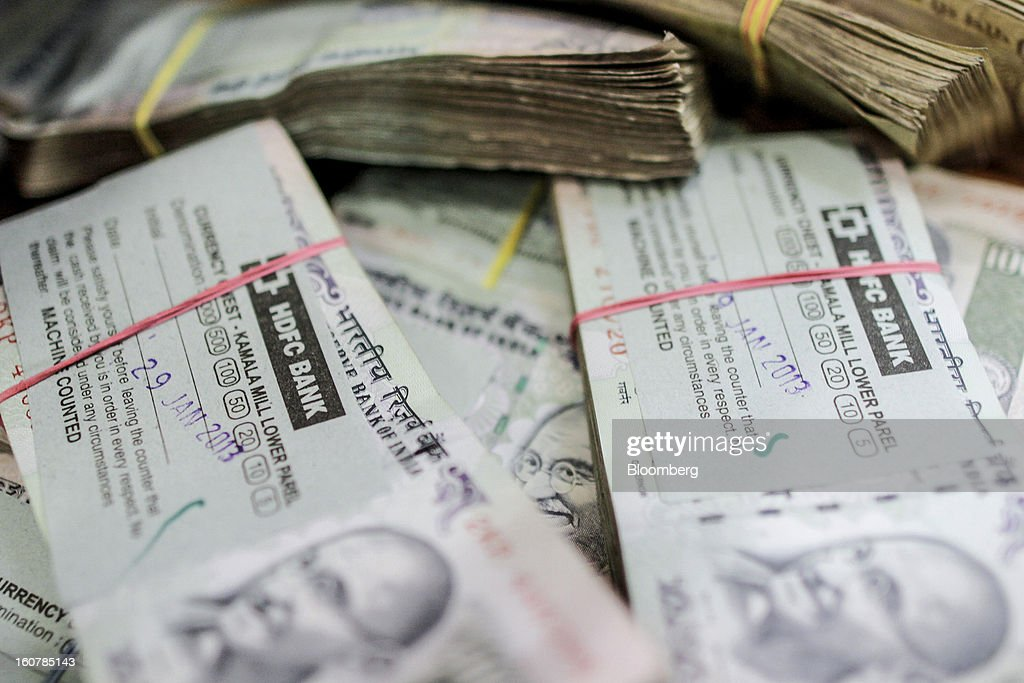 Bundles of Indian 100 rupee banknotes are seen at a HDFC Bank Ltd. bank branch in Mumbai, India, on Friday, Feb. 1, 2013. HDFC Bank, India's second-largest lender by market value, is seeking to expand in the rural market of the world's second-most populated nation to bolster profits as competition in its cities intensifies. Photographer: Dhiraj Singh/Bloomberg via Getty Images
