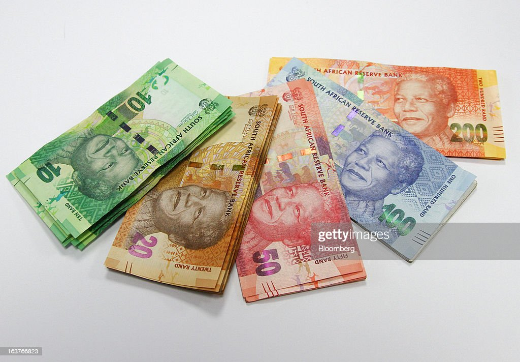 Bundles of mixed denomination rand currency banknotes are arranged for a photograph at a First National Bank (FNB) branch in Johannesburg, South Africa, on Friday, March 15, 2013. A recovery in mining and manufacturing is giving South Africa's rand and bonds a breather amid concern that growth is slowing while inflation accelerates. Photographer: Nadine Hutton/Bloomberg via Getty Images