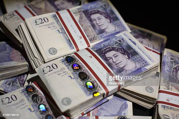 Bundles of twenty pound sterling banknotes are arranged for a photograph in London UK on Thursday March 6 2014 The pound was 05 percent from the...