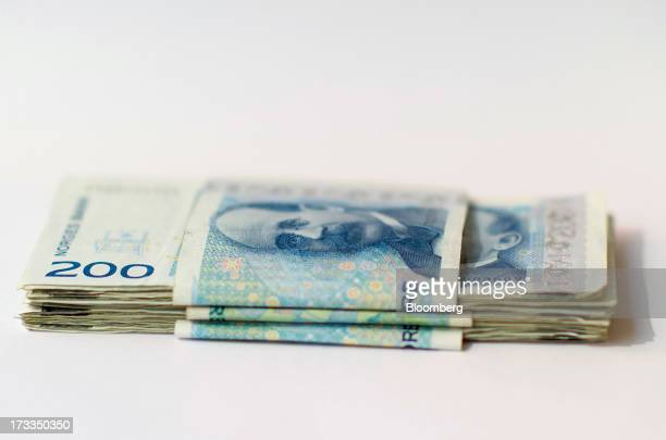 Bundles of two hundred krone currency notes sit in this arranged photograph in Oslo Norway on Friday July 13 2013 Norway's underlying inflation rate...