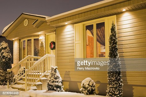 Bungalow style residential home illuminated in winter at for Home decorations canada
