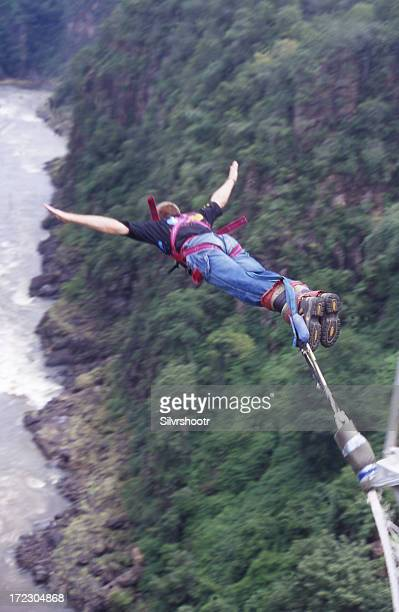 Bungee jumper in mid air with arms outstretched