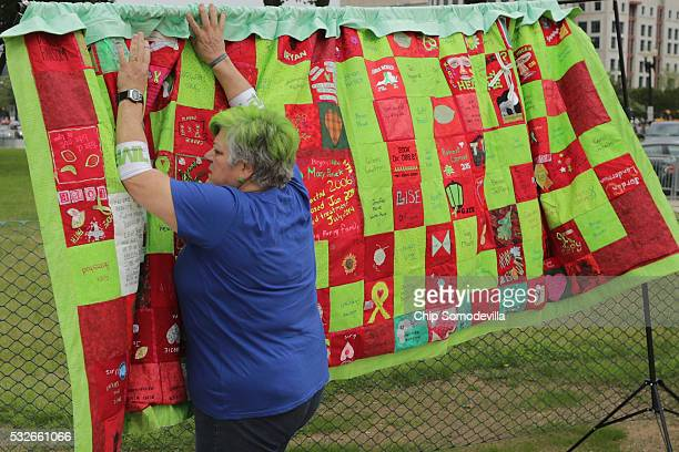 Bunny Woloszczak of Hurleyville New York works to display The Lyme Quilt near the US Capitol Reflecting Pool May 19 2016 in Washington DC Red panels...