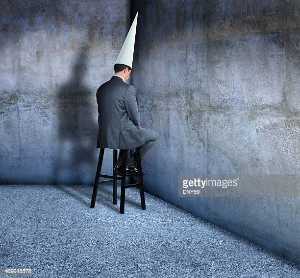 Bunsinessman in dunce cap sits on a stool in corner