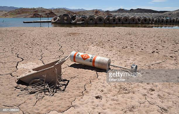 A buoy warning 'no boats' lies in cracked mud at the abandoned Echo Bay Marina in front of old tires once used as a breakwater on July 13 2014 in the...