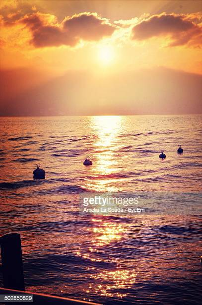 Buoys in sea at sunset