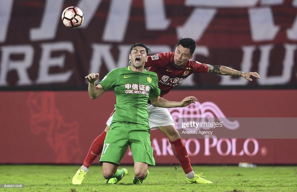 Burak Yilmaz (L) of Beijing Guoan in action against Zhang Linpeng (R) of Guangzhou Evergrande during the China Super League match between Guangzhou Evergrande and Beijing Guoan at Tianhe Sports Center on March 5, 2017 in Guangzhou, China.