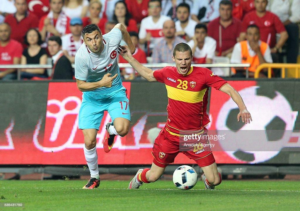 Burak Yilmaz (L) of Turkey and Aleksanar Sofranac (R) of Montenegro vie for the ball during the friendly football match between Turkey and Montenegro at Antalya Ataturk Stadium in Antalya, Turkey on May 29, 2016.