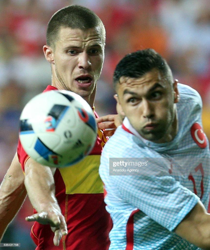 Burak Yilmaz (R) of Turkey and Aleksanar Sofranac (L) of Montenegro vie for the ball during the friendly football match between Turkey and Montenegro at Antalya Ataturk Stadium in Antalya, Turkey on May 29, 2016.