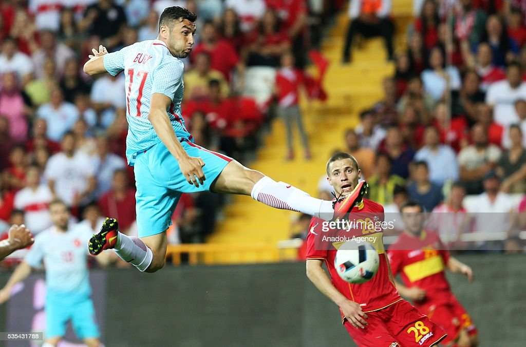 Burak Yilmaz (L) of Turkey and Aleksandar Sofranac (R) of Montenegro vie for the ball during the friendly football match between Turkey and Montenegro at Antalya Ataturk Stadium in Antalya, Turkey on May 29, 2016.