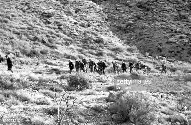 Burdened with ropes and tarpaulin these soldiers and possemen start climbing 8500 foot Double Peak near Las Vegas to begin grim and dangerous task of...