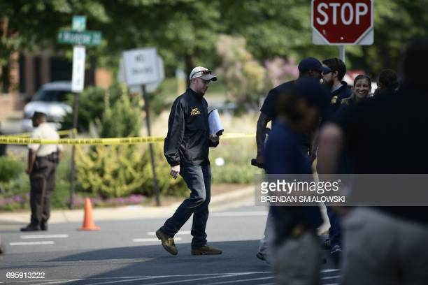 A Bureau of Alcohol Tobacco Firearms and Explosive police member walks near the crime scene of an early morning shooting in Alexandria Virginia June...