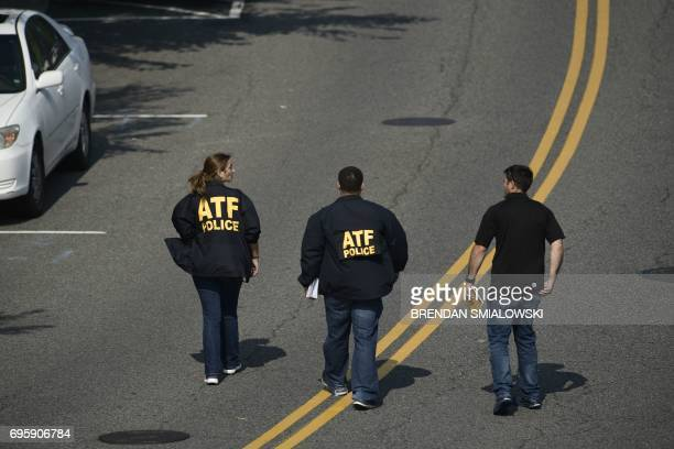 Bureau of Alcohol Tobacco Firearms and Explosive police members walk near the crime scene of an early morning shooting in Alexandria Virginia June 14...