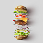 Top view of cheeseburger ingredients represented against white background. Hamburger or sandwich with cheese, tomato, beef, etc.