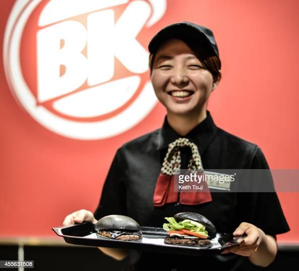 Burger King employee Minako Matsumoto displays two black hamburgers at a Burger King Japan's restaurant on September 18 2014 in Tokyo Japan The black...
