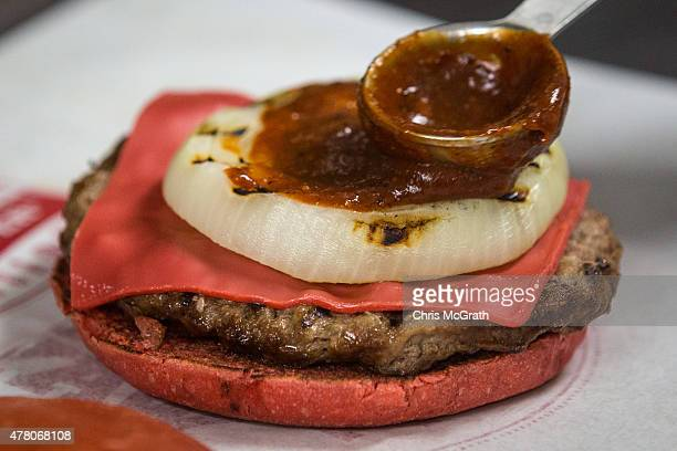 Burger King employee spreads hot sauce on one of the new 'Red' burgers at a store on June 22 2015 in Tokyo Japan The AKA Samurai Burger and the...