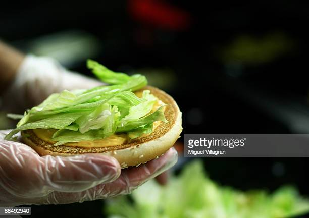 Burger King staff member makes a Whopper Burger with lettuce during the opening of the first European Whopper Bar on June 15 2009 in Munich Germany...