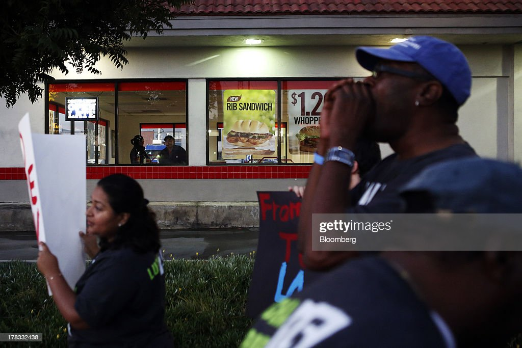 Burger King Worldwide Inc. employees look out of a window as fast-food workers and supporters organized by the Service Employees International Union (SEIU) protest outside of a restaurant in Los Angeles, California, U.S., on Thursday, Aug. 29, 2013. Fast-food workers in 50 U.S. cities plan to walk off the job today, ratcheting up pressure on the industry to raise wages and demanding the right to wages of $15 an hour, more than double the federal minimum of $7.25. Photographer: Patrick T. Fallon/Bloomberg via Getty Images