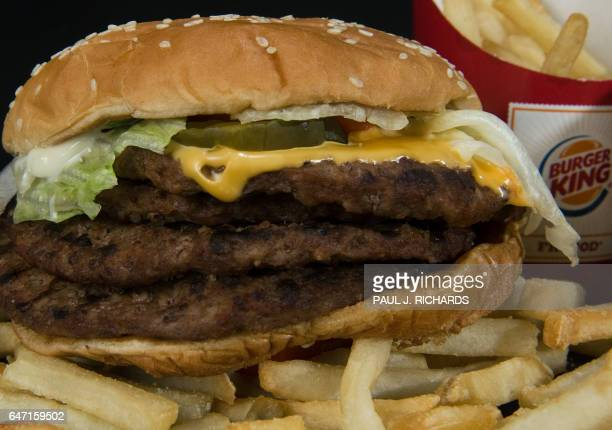 Burger King's 'BK Quad Stacker' hamburger with four beef patties topped with bacon cheese sauce lettuce pickles and onions is seen August 19 in...