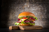 Burger with beef, cheese and tomatoes, American fast food. Gray background