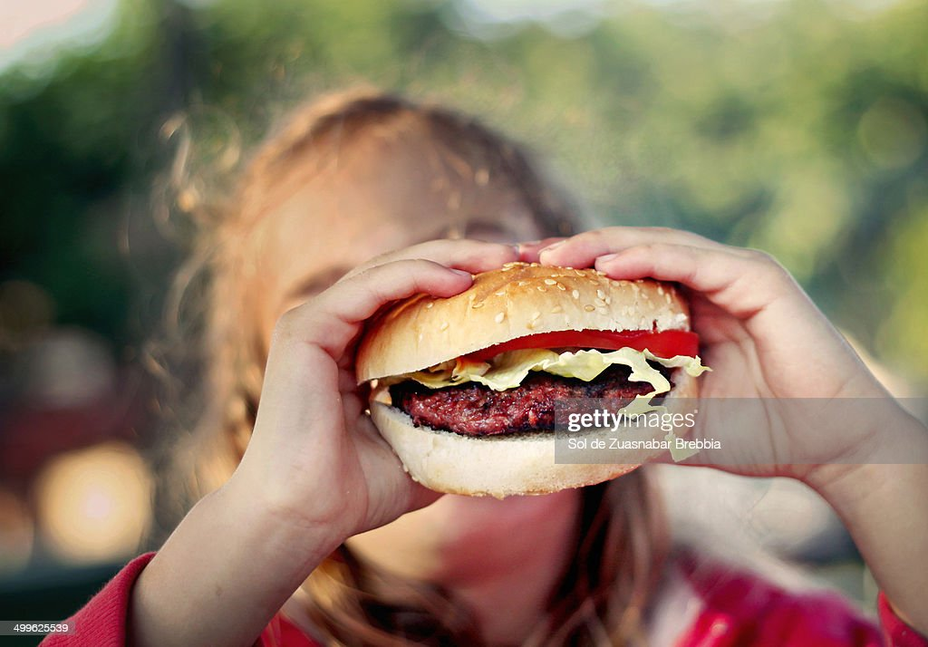 Burger with lettuce and tomato in a girl's hands