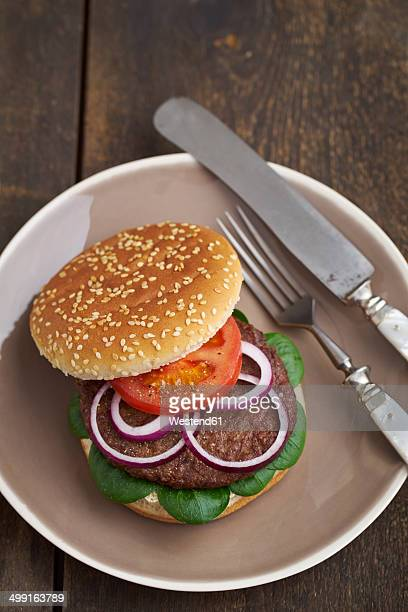 Burger with mincemeat, tomato, lamb's lettuce and red onions on plate