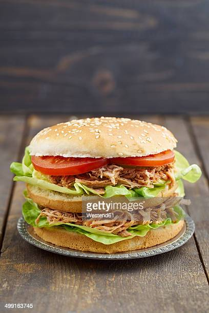 Burger with pulled pork, tomato and salad on plate