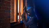 Hooded masked burglar forcing open a window in a home.