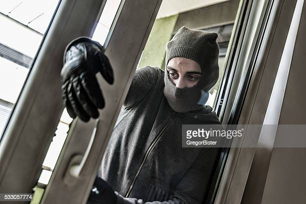 Burglar breaking into a house