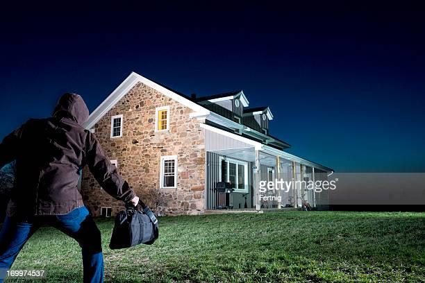 Burglar creeping up on a house