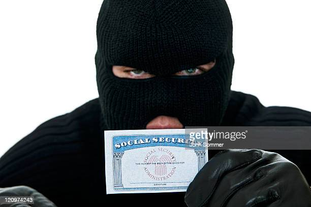 Burglar holding a social security card for ID theft