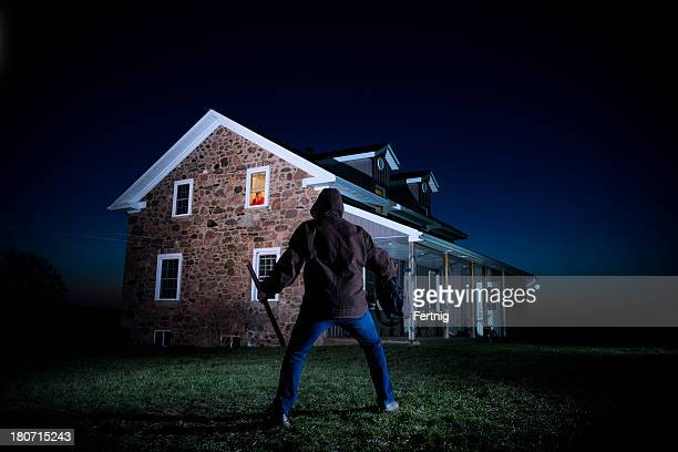 Burglar outside house at night with the homeowner watching