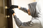 Profile view of a man with a hoodie trying to pick a lock in a house and forcing his entry