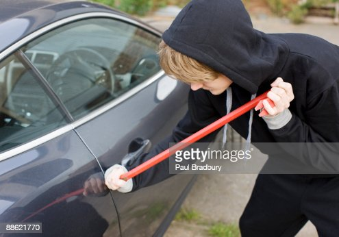 Burglar prying car window open with crowbar : Stock Photo
