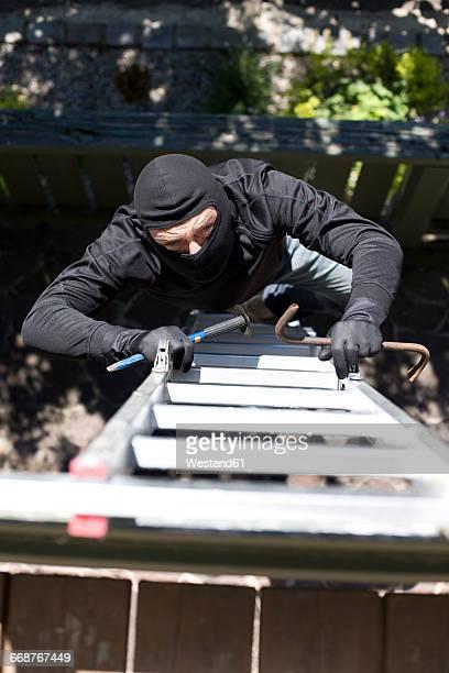 Burglar with crowbar climbing up ladder at house wall