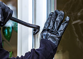 A burglar opens a window with a breaker. He wears gloves and lifts the window.