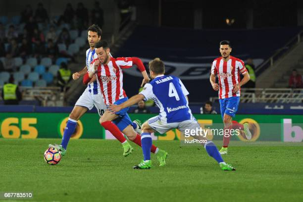 Burgui of Sporting Gijon duels for the ball with Illarramendi of Real Sociedad during the Spanish league football match between Real Sociedad and...