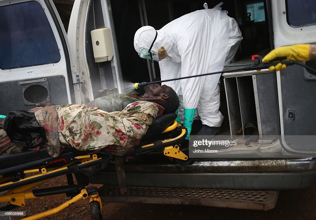 A burial team disinfects an Ebola victim while collecting him for cremation on October 2 2014 in Monrovia Liberia Eight Liberian Red Cross burial...