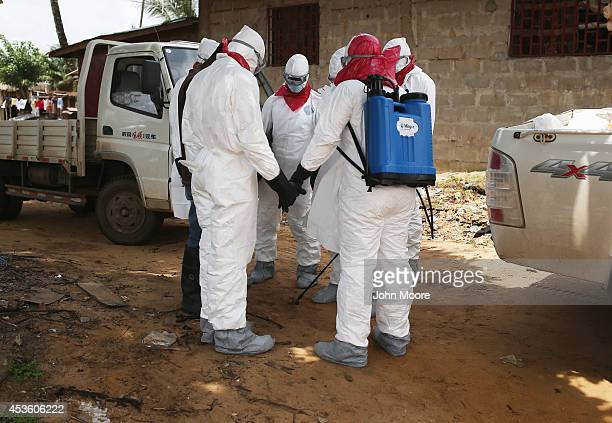 A burial team from the Liberian health department prays before entering a house to remove the body of a woman suspected of dying of the Ebola virus...