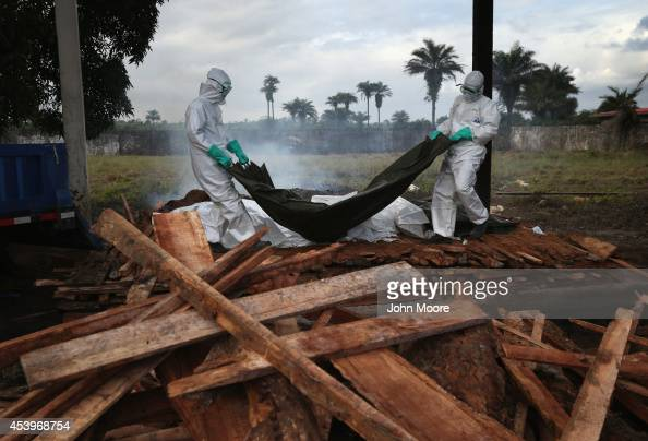 A burial team from the Liberian Ministry of Health unloads the bodies of Ebola victims onto a funeral pyre at a crematorium on August 22 2014 in...