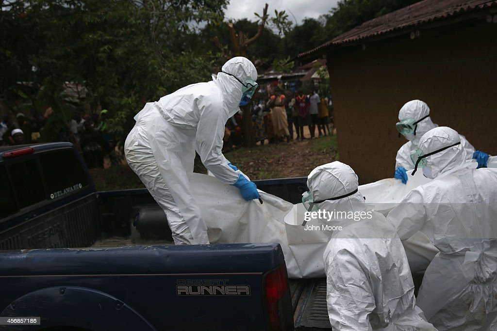A burial team from the Liberian Red Cross carries the body of an Ebola victim from his home on October 8 2014 near Monrovia Liberia The Ebola...