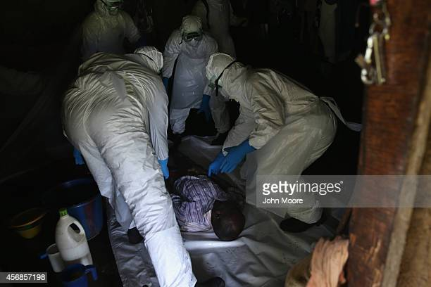A burial team from the Liberian Red Cross collects the body of an Ebola victim from his home on October 8 2014 near Monrovia Liberia The Ebola...