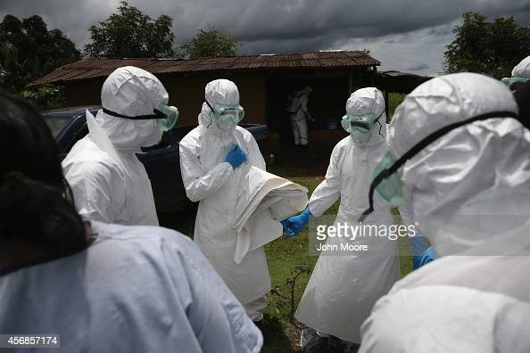 A burial team from the Liberian Red Cross prays before collecting the body of an Ebola victim from his home on October 8 2014 near Monrovia Liberia...