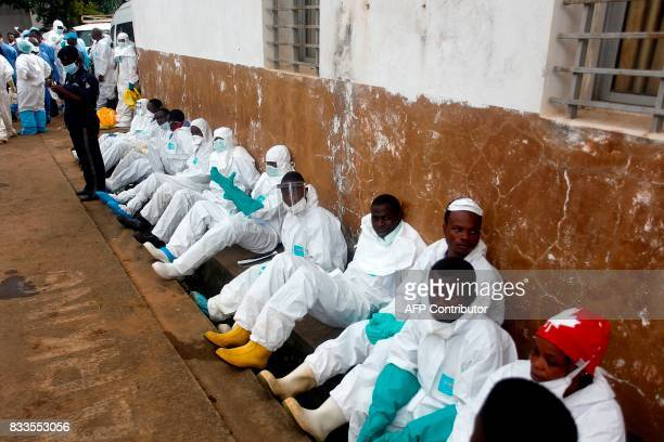 TOPSHOT Burial team members rest outside an hospital in Freetown on August 16 2017 The first mass burials of victims of Sierra Leone's devastating...